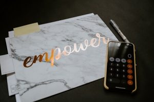 black desk with iPhone set to calculator function, a silver pen, a marbled paper with the word 'empower' in gold